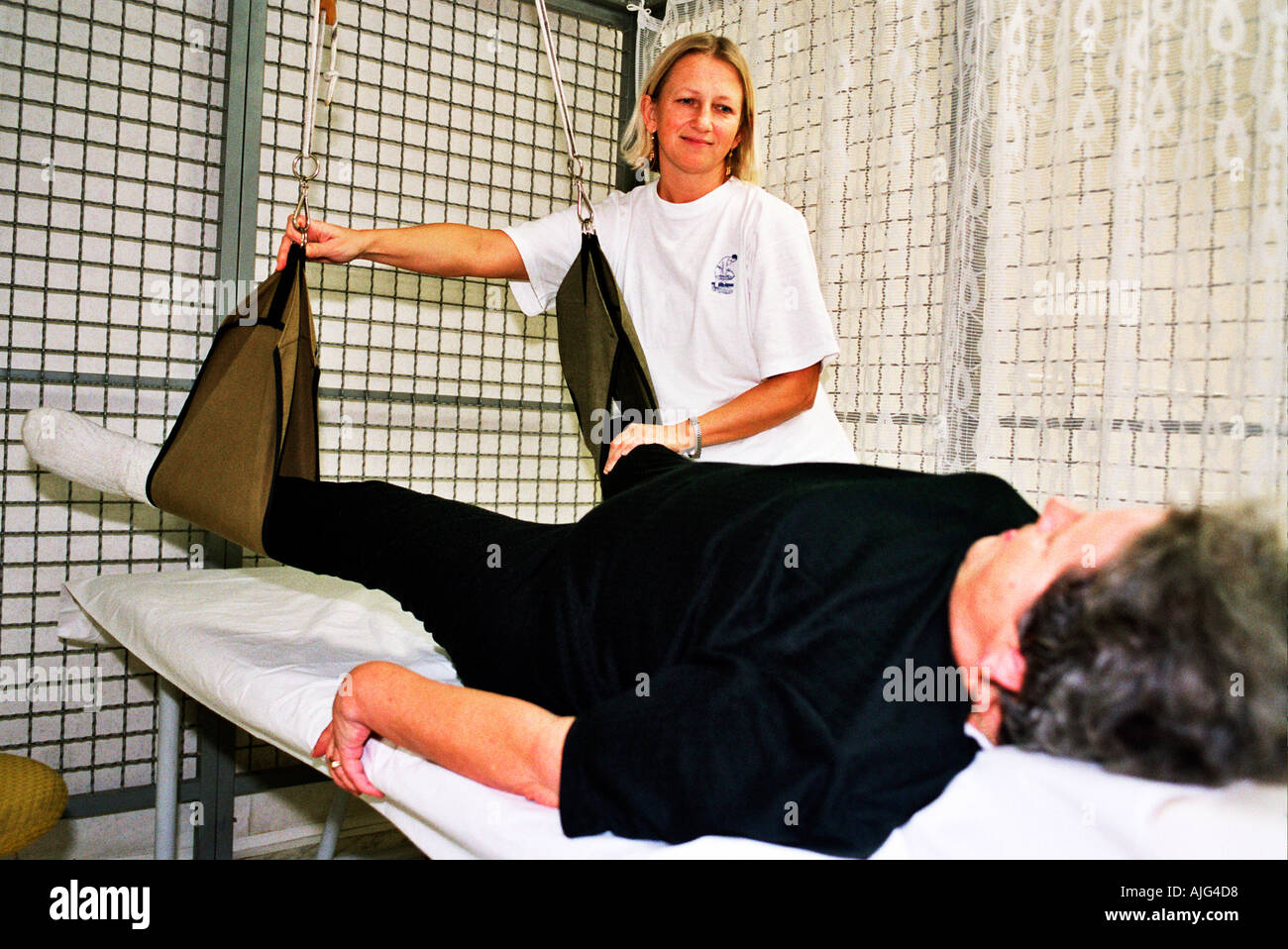 Older woman receiving care for mobility physiotherapy - Stock Image