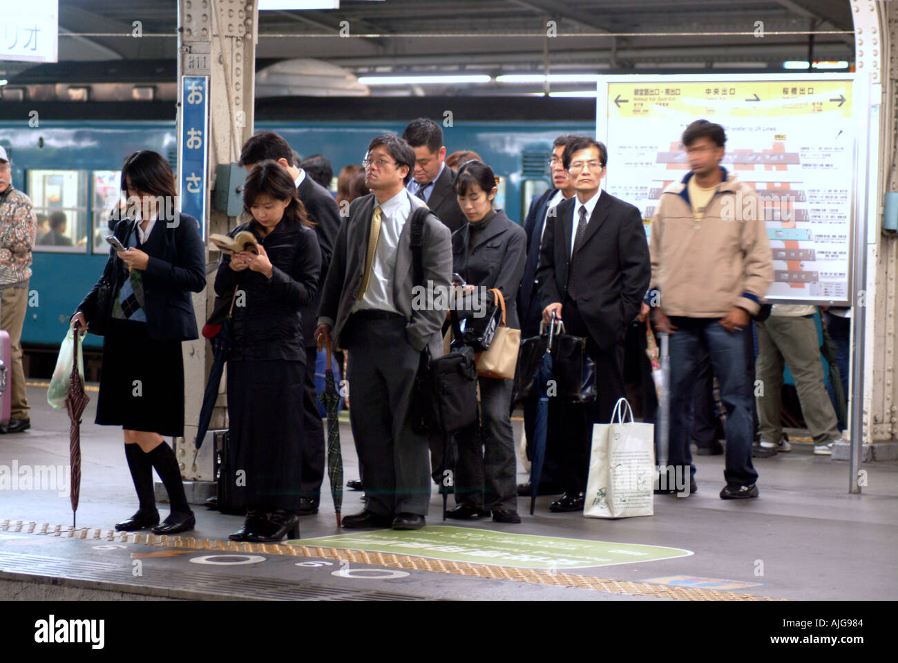 People waiting in a queue on a railway platform Osaka Japan - Stock Image