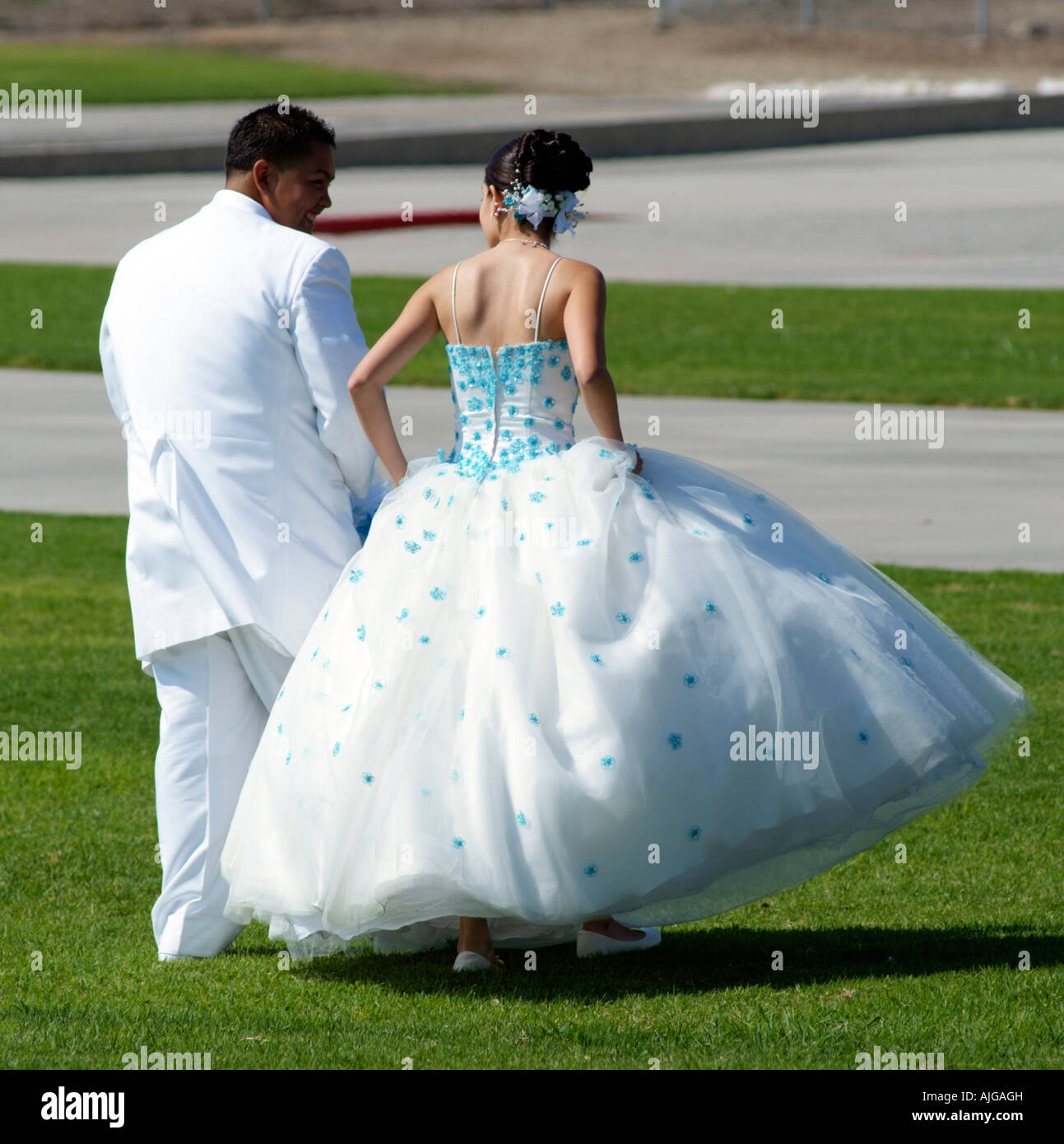A rea view of a Groom in White Suit with Bride Wearing Blue and ...