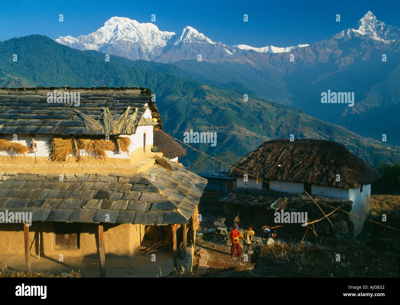 Traditional Nepalese house with Annapurna Machhapuchhre beyond the Annapurna Himalaya Nepal - Stock Image