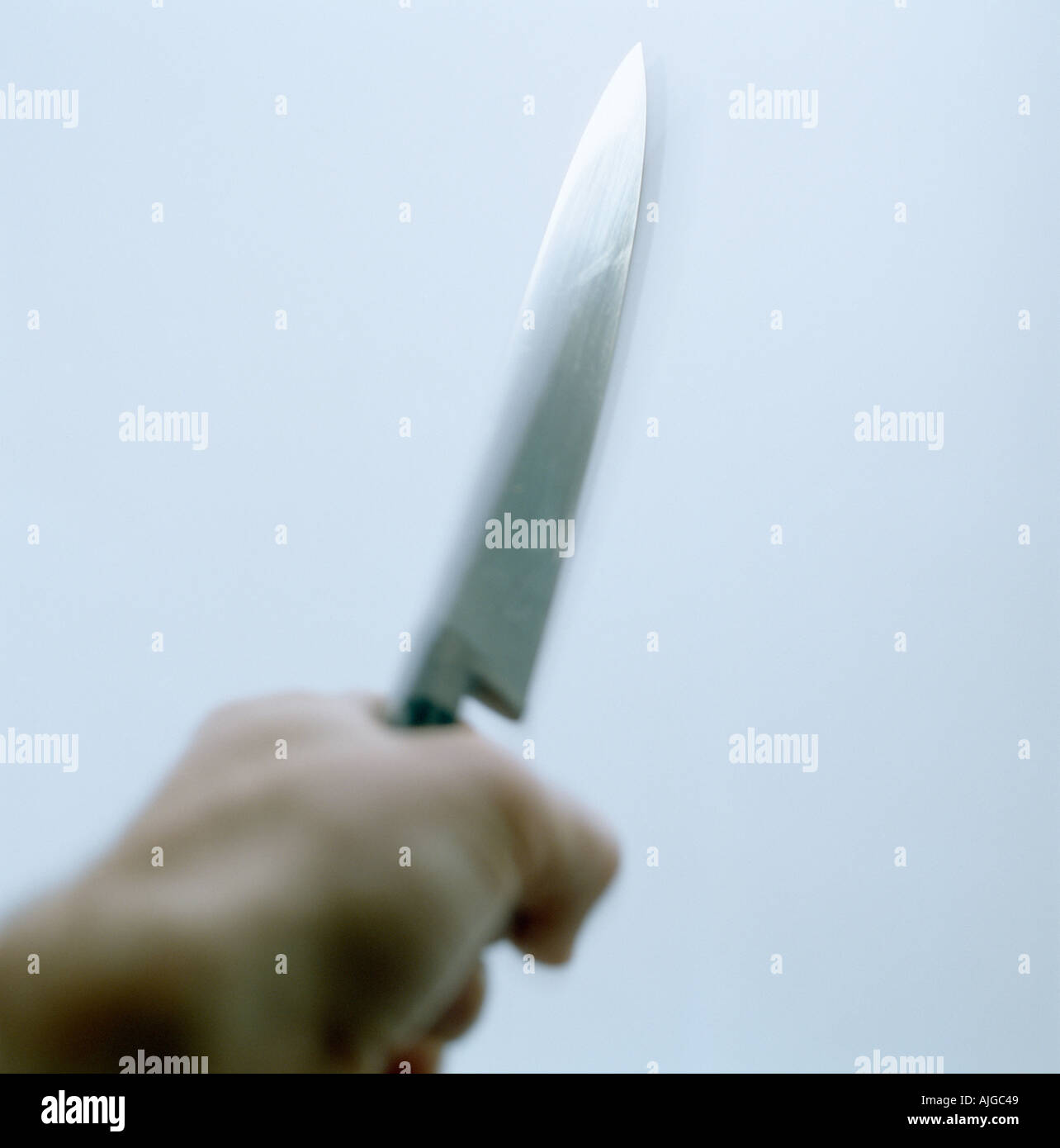 Knife being held in attacking threatening manner - Stock Image