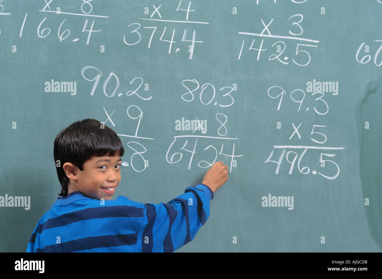 Vietnamese Student writing math equations on a blackboard during ...