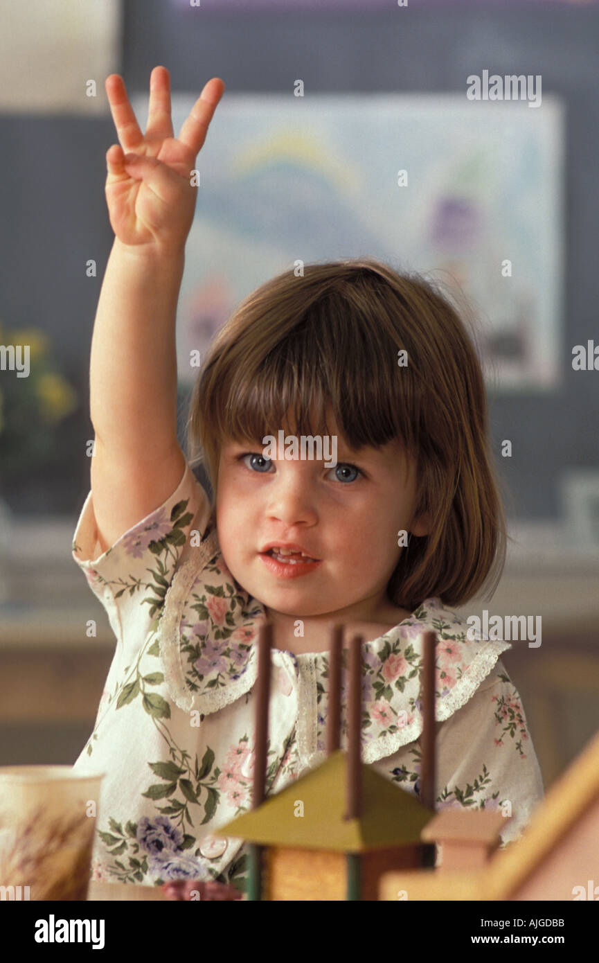Portrait Caucassian female student raising hand in preschool class - Stock Image