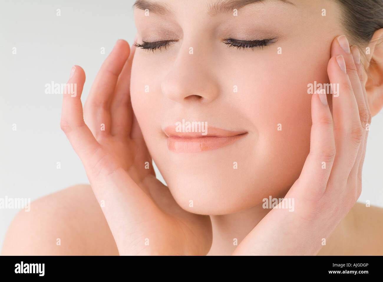 Young woman touching her cheeks - Stock Image