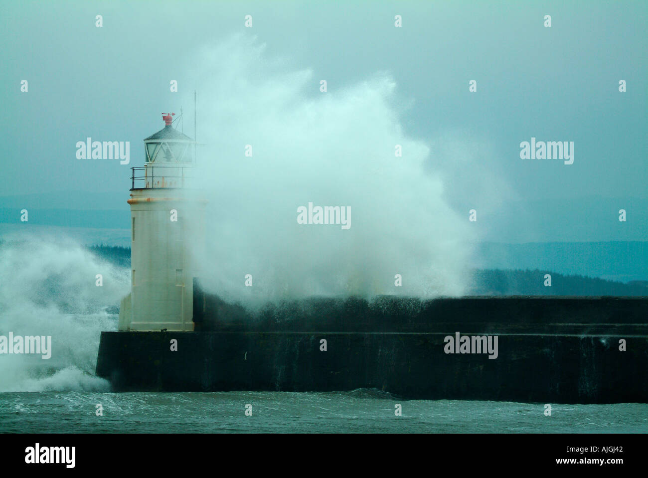 Waves crashing over lighthouse during storm Stock Photo