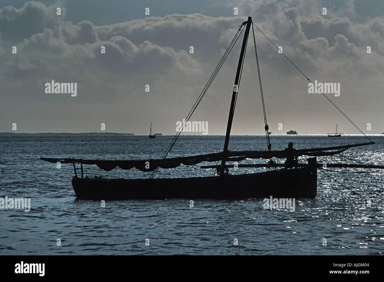 Dhow silhouetted against the morning sunlight Mafia island south of Zanzibar Tanzania East Africa - Stock Image