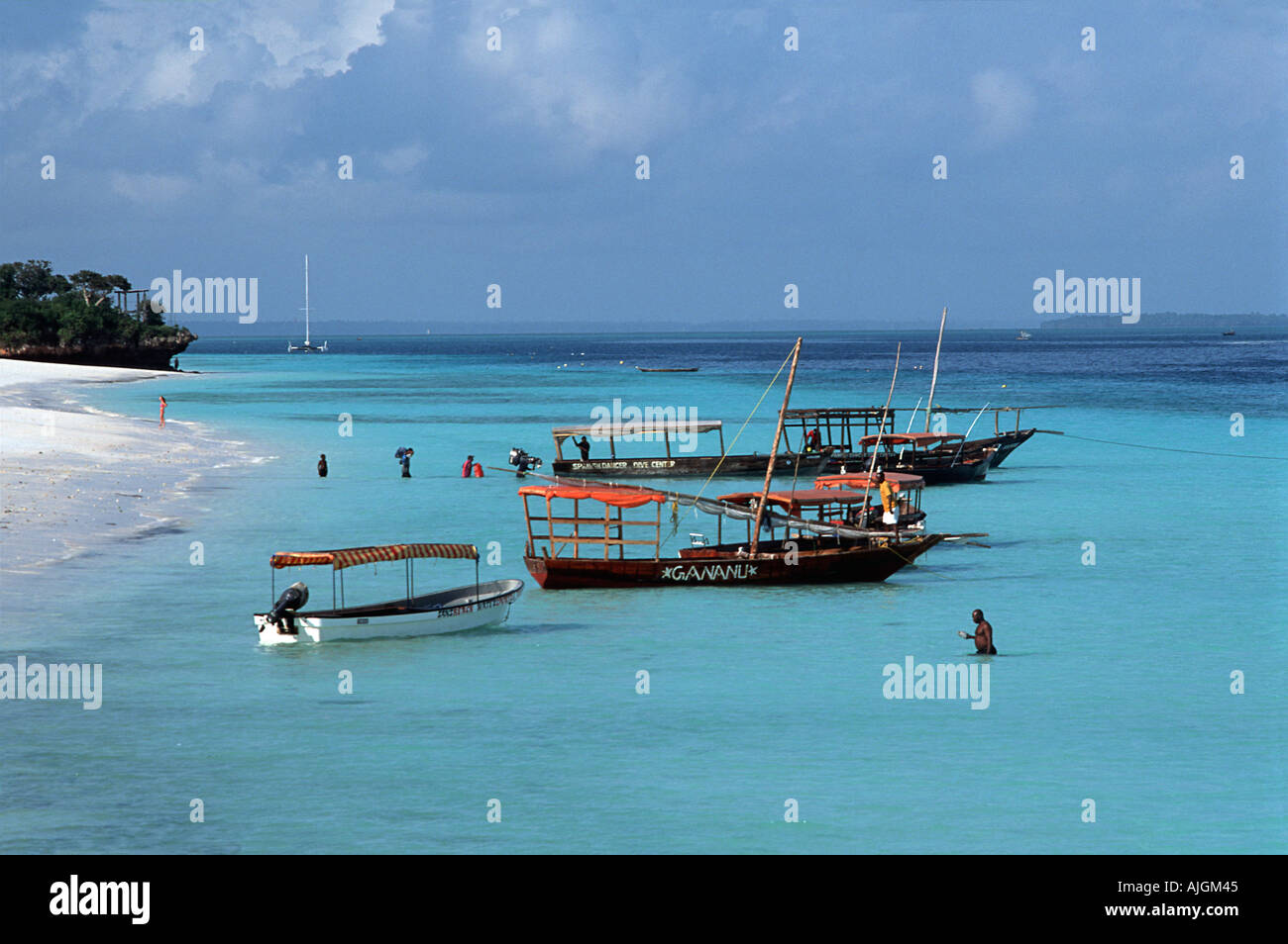 Boats anchored off the beach at Nungwi Unguja Zanzibar Loading up a dive boat in the background Tanzania East Africa - Stock Image