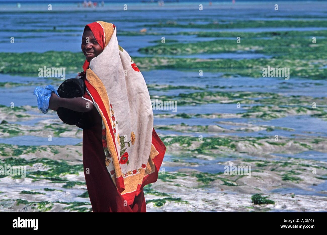 Zanzibari woman in a colouful kanga cloth turns and smiles Nungwi Unguja Zanzibar Tanzania East Africa - Stock Image