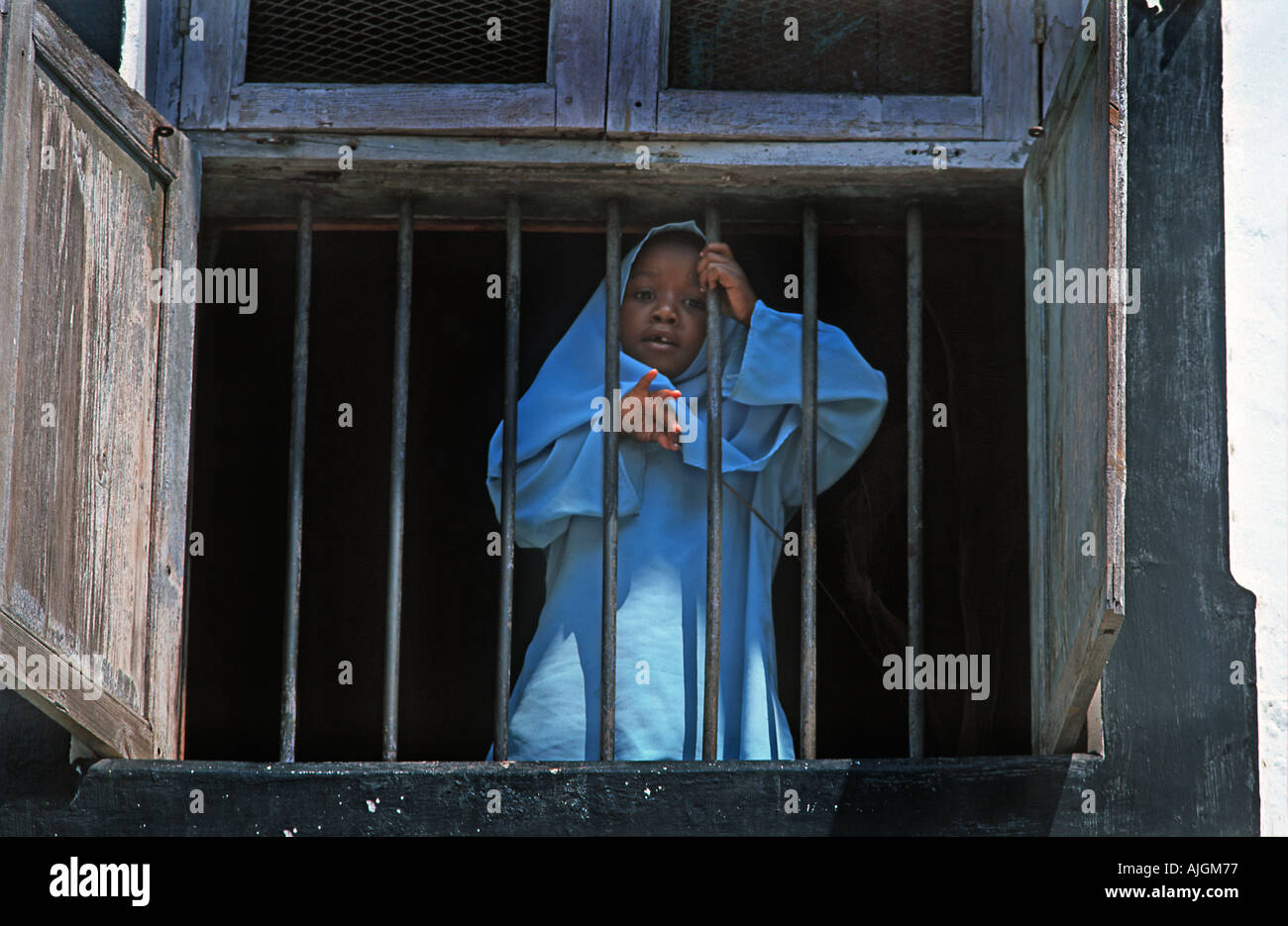 Girl in a blue robe standing at a window overlooking the street Stone Town Unguja Zanzibar Tanzania East Africa - Stock Image