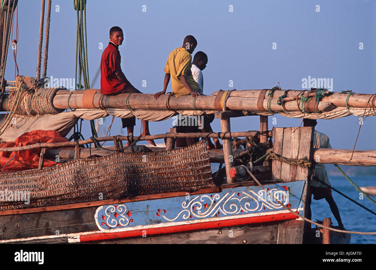 Fishermen seated on the mast of their dhow Stone Town dhow harbour at sunset Unguja Zanzibar Tanzania - Stock Image
