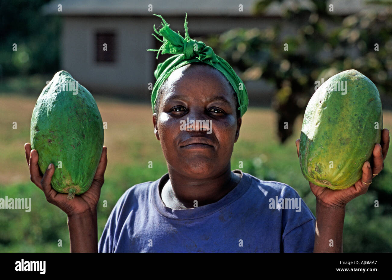 Friendly market vendor with a fresh papaya Arusha Tanzania East Africa - Stock Image