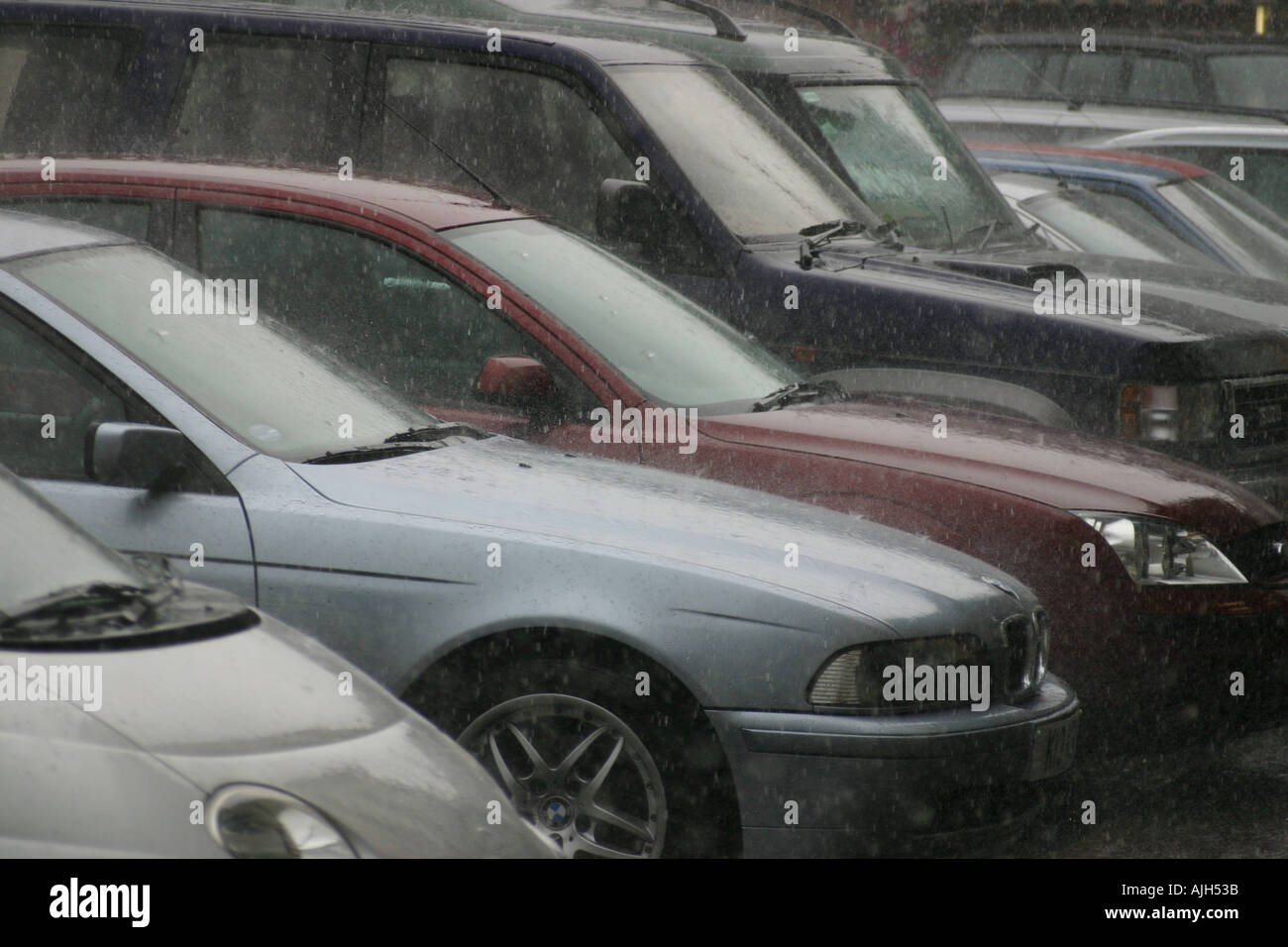 Parked cars in a summer rainstorm in Devon uk - Stock Image
