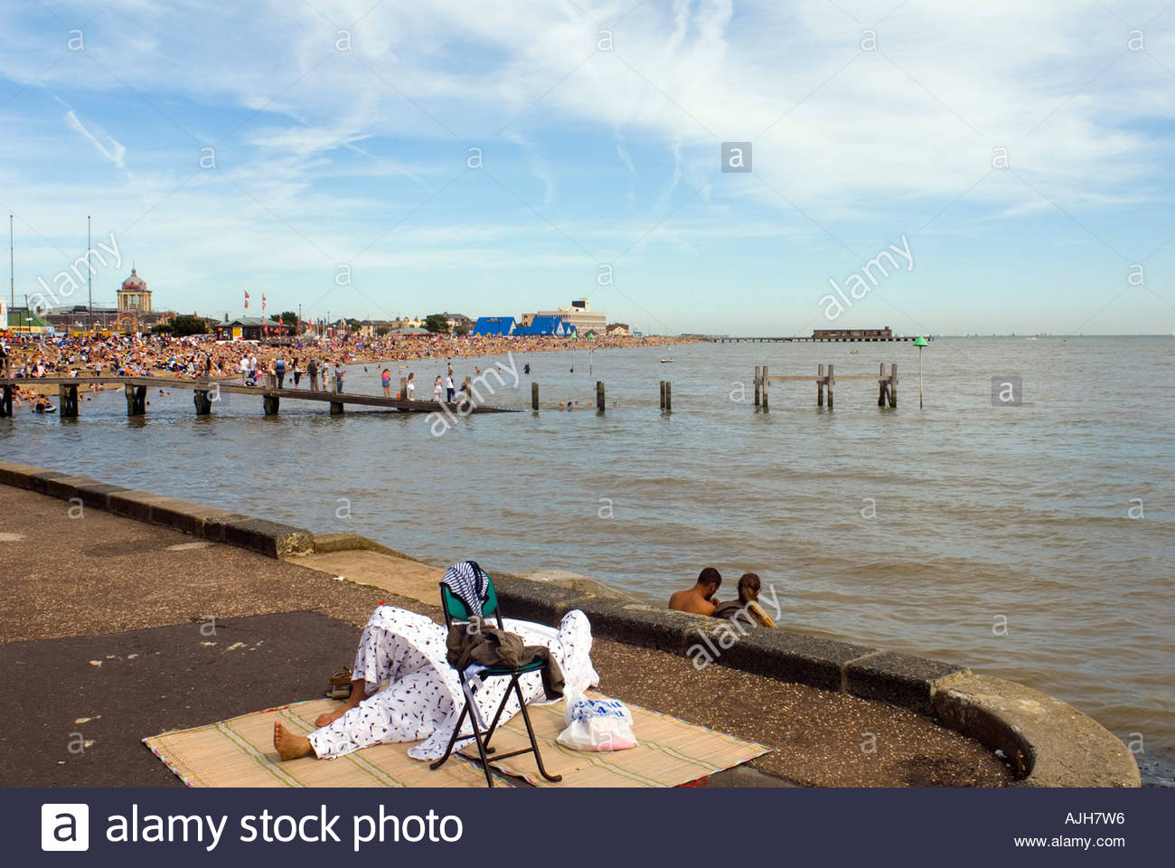 Asian woman sleeping on the promenade at Southend on Sea Essex South East England UK - Stock Image