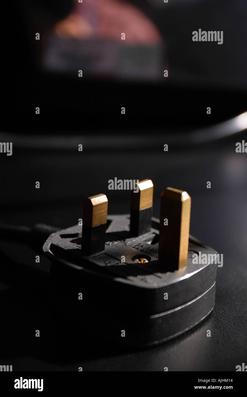 Electric plug on black background with appliance - Stock Image