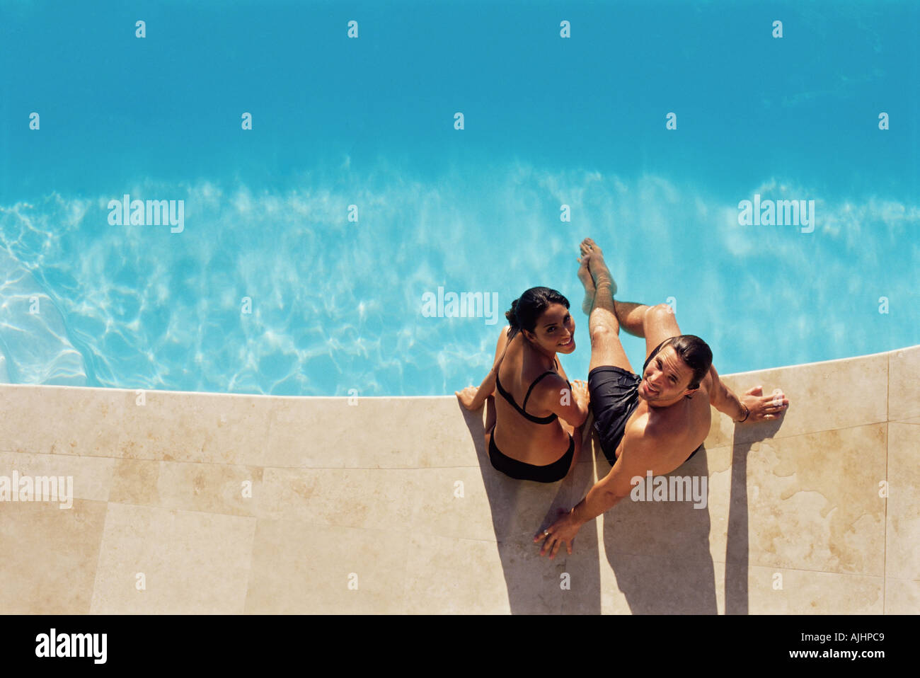Couple sitting on the edge of swimming pool - Stock Image