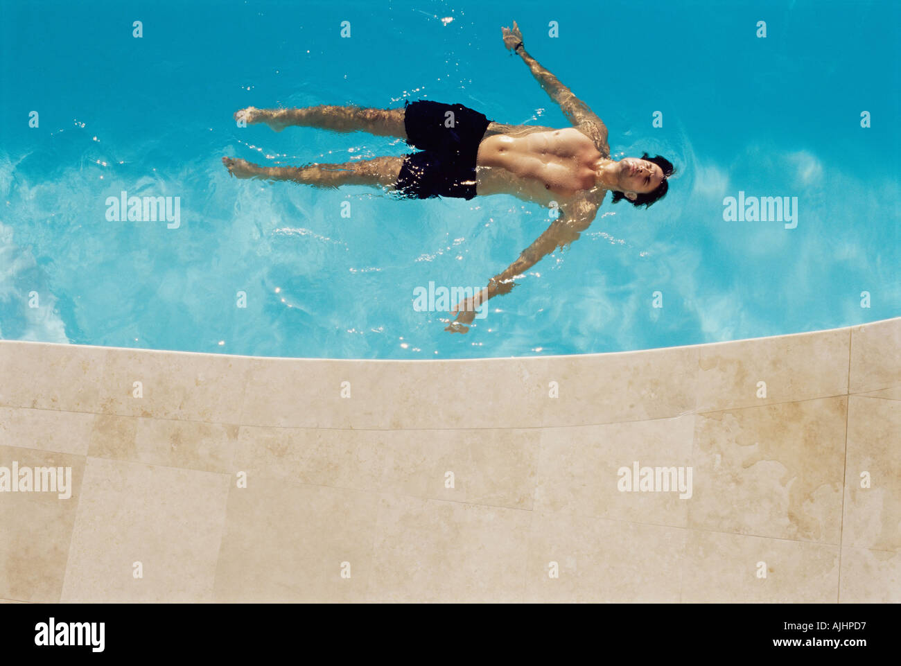 Man floating in swimming pool - Stock Image