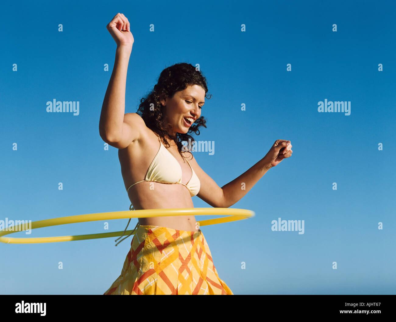Woman playing with hula hoop - Stock Image