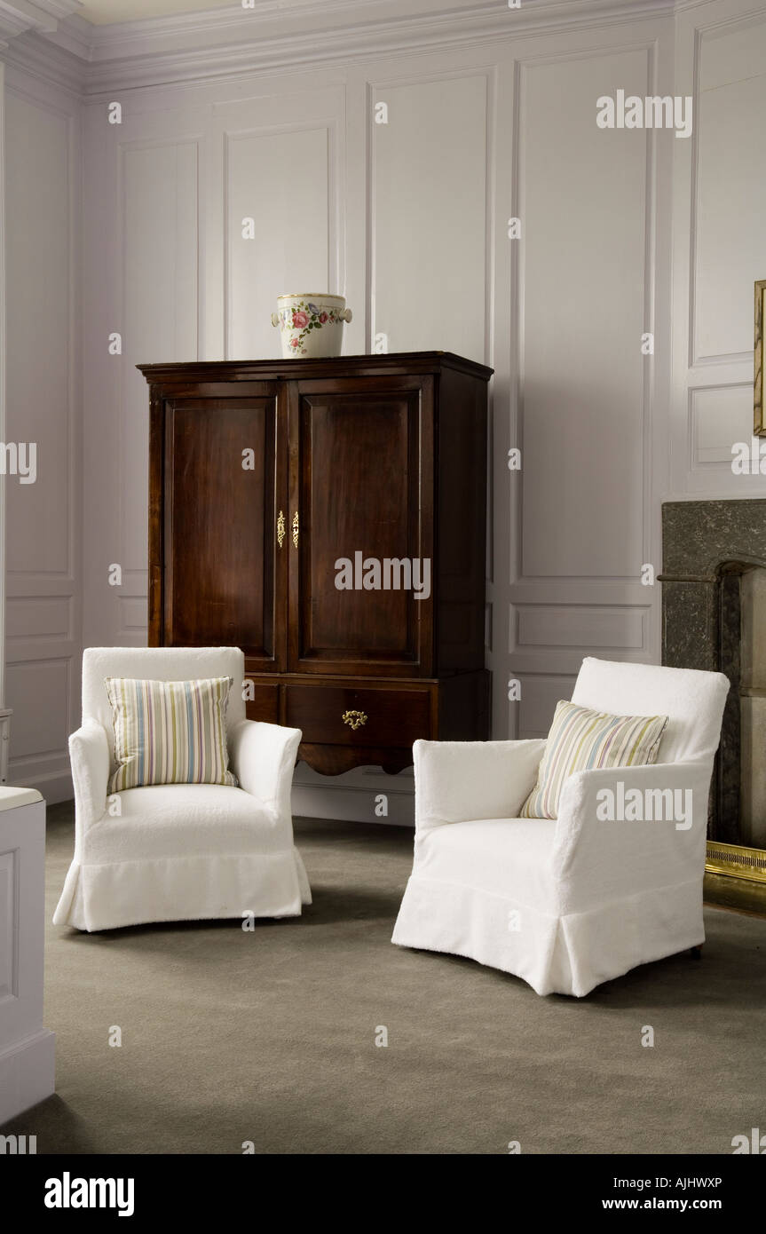 White armchairs and cupboard in wood panelled room in 17th century Irish castle - Stock Image