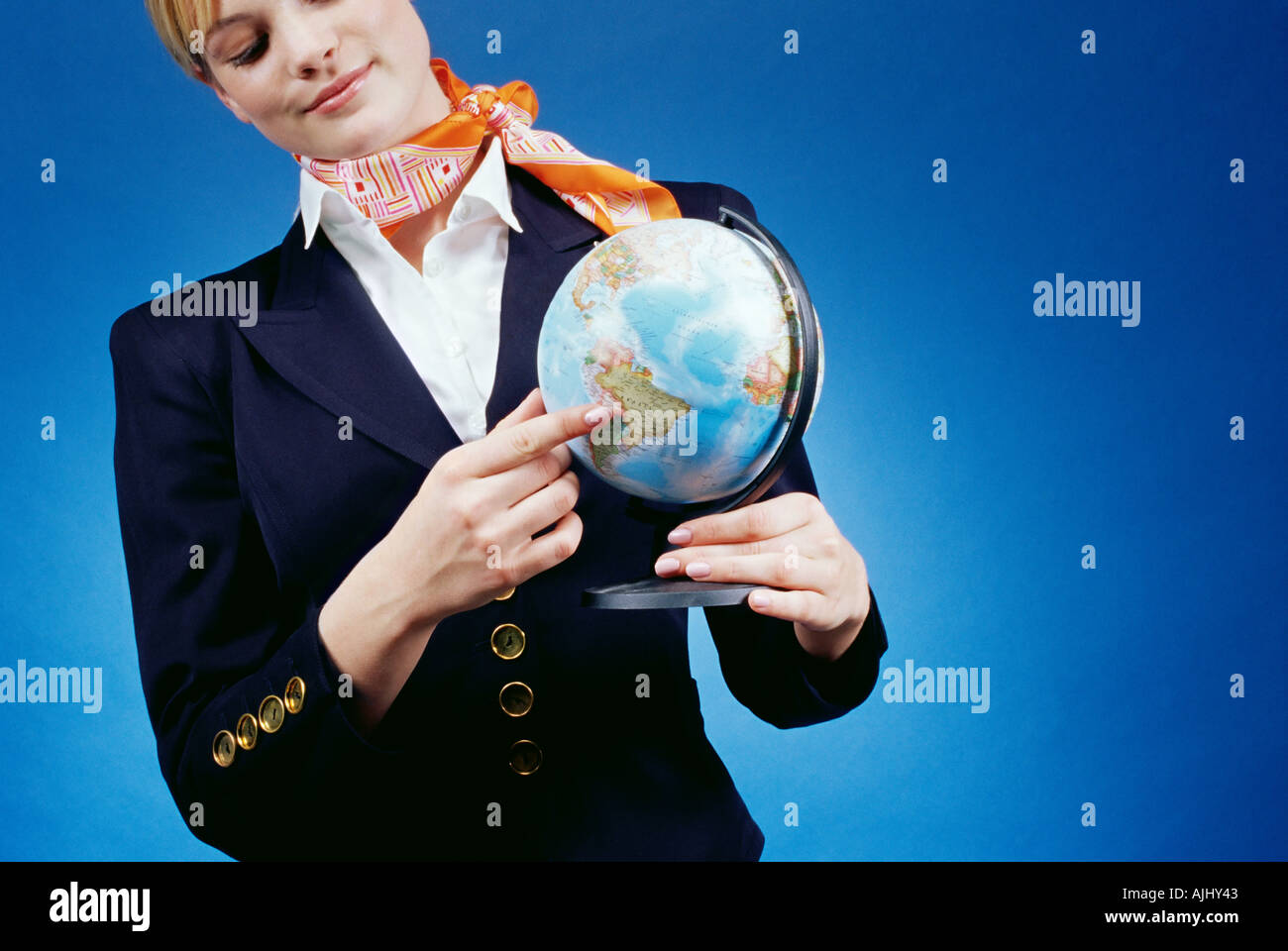 Air hostess pointing to a globe - Stock Image