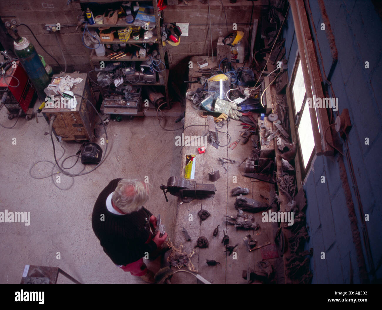 Mature male in metalwork workshop - Stock Image