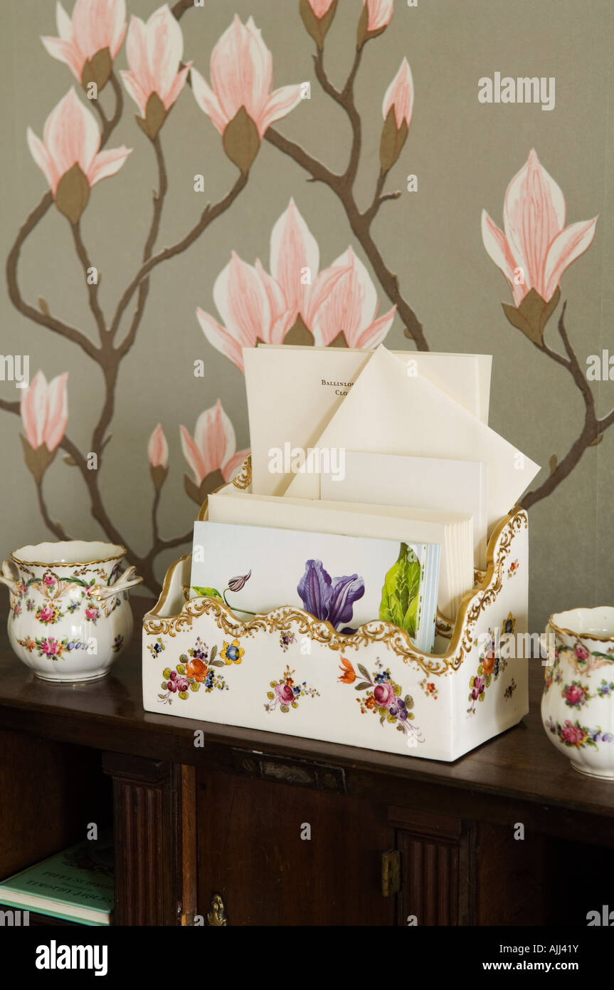 Floral letter holder with matching china pots and designer floral wall paper behind - Stock Image