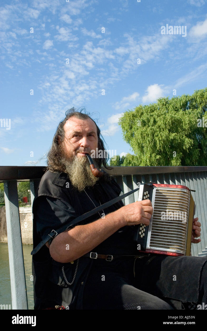 Pipe smoking busker playing the accordion on a Seine bridge Paris France - Stock Image