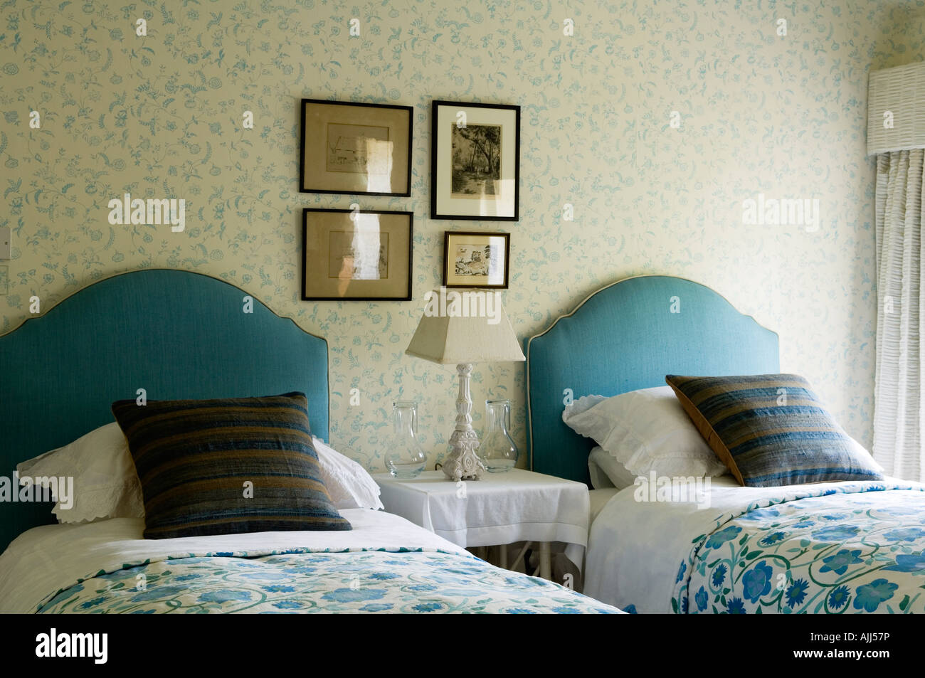 Bedroom with turquoise twin beds and designer patterned wall paper in 17th century Irish castle. - Stock Image