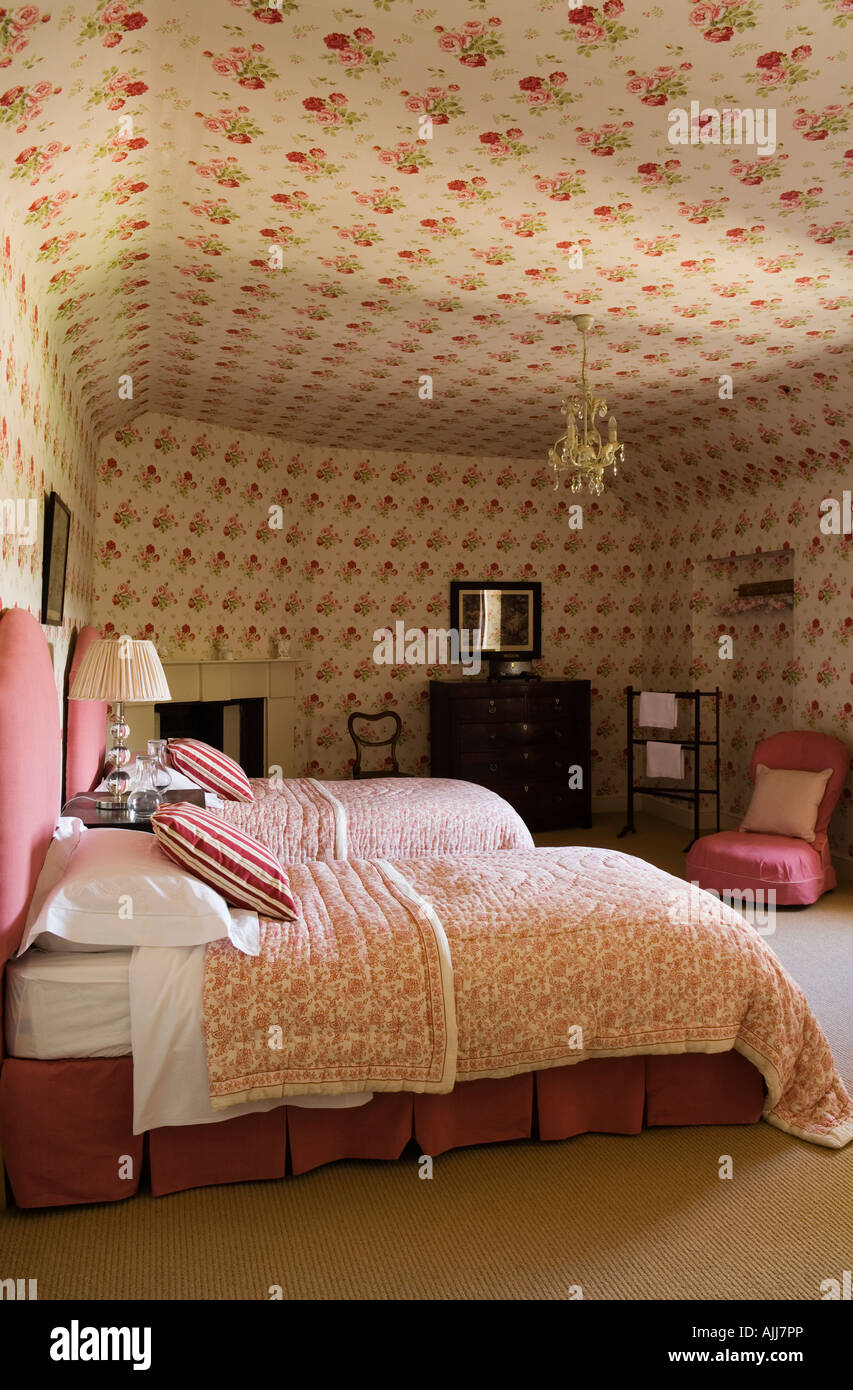 Bedroom with quilt covered twin beds and pink floral patterned ceiling and wallpaper - Stock Image