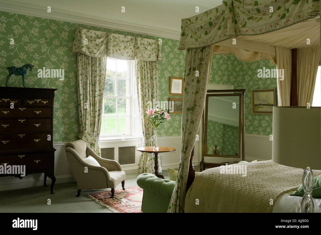 Bedroom with fourposter bed and green patterned wall paper in 17th century Irish castle - Stock Image