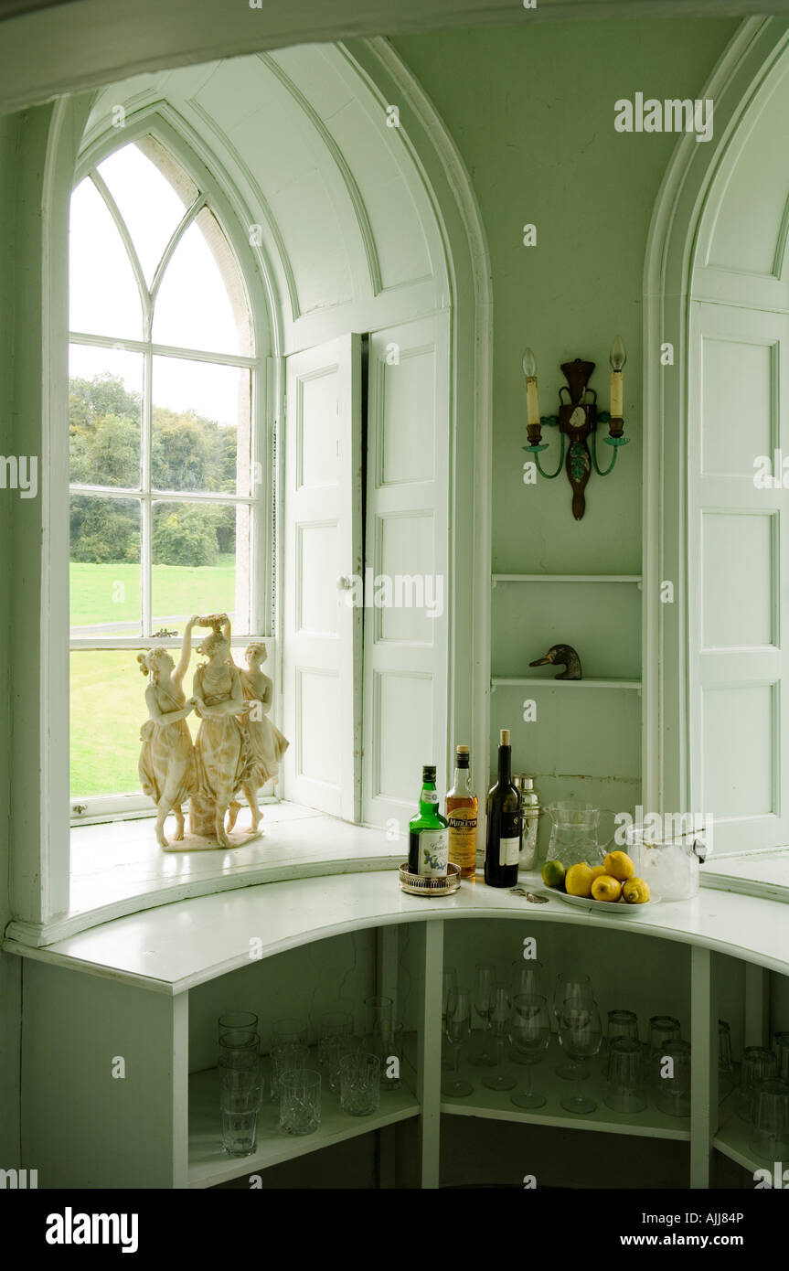 Recessed gothic window with shutters and glassware shelf with drinks bottles - Stock Image