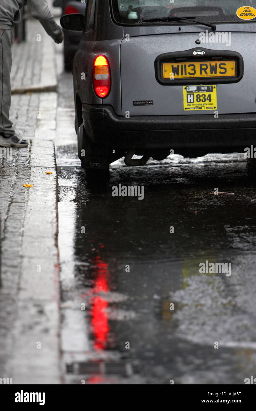 private london style taxi pulled into side of the road with puddles to pick up male fare in belfast city centre - Stock Image