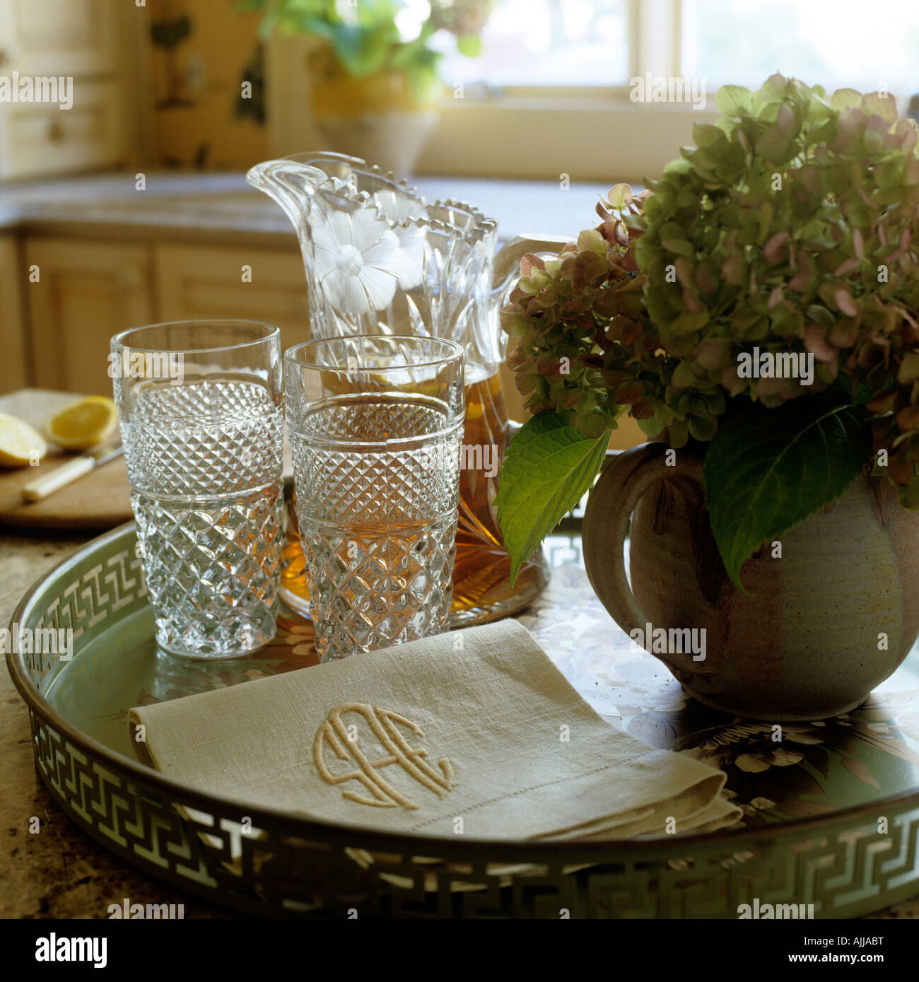 Refreshment tray with cut glassware, napkins and hydrangea in jug - Stock Image