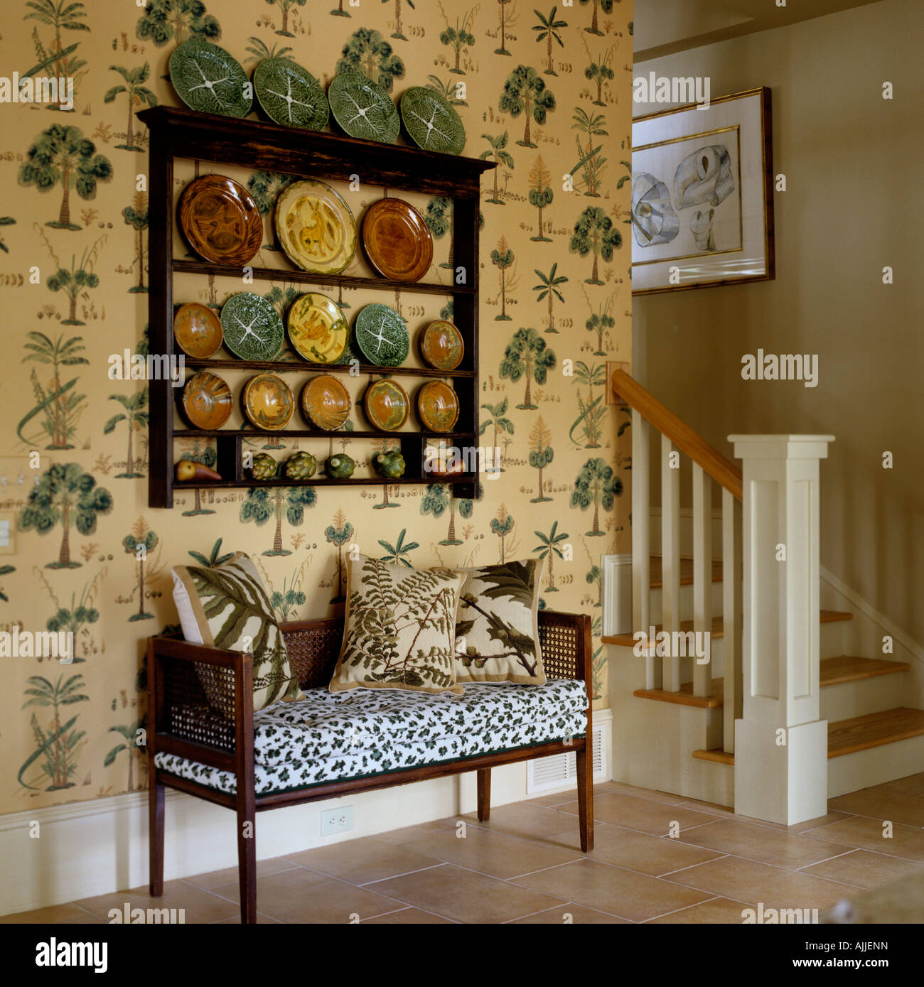 Hallway with Brunschwig wallpaper, plate display and upholstered settee. - Stock Image