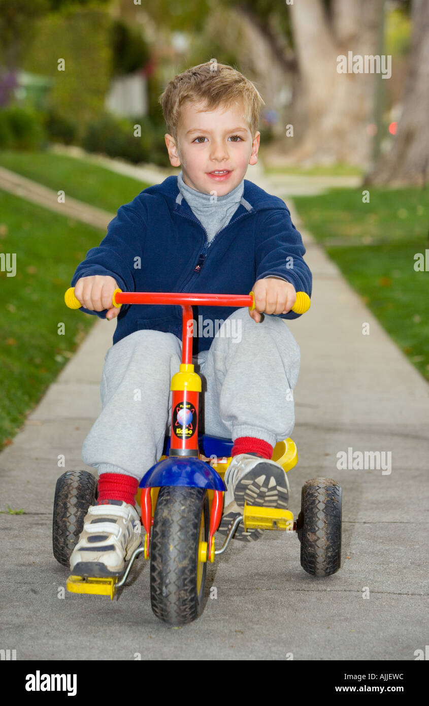 four year old boy rides tricycle down sidewalk - Stock Image