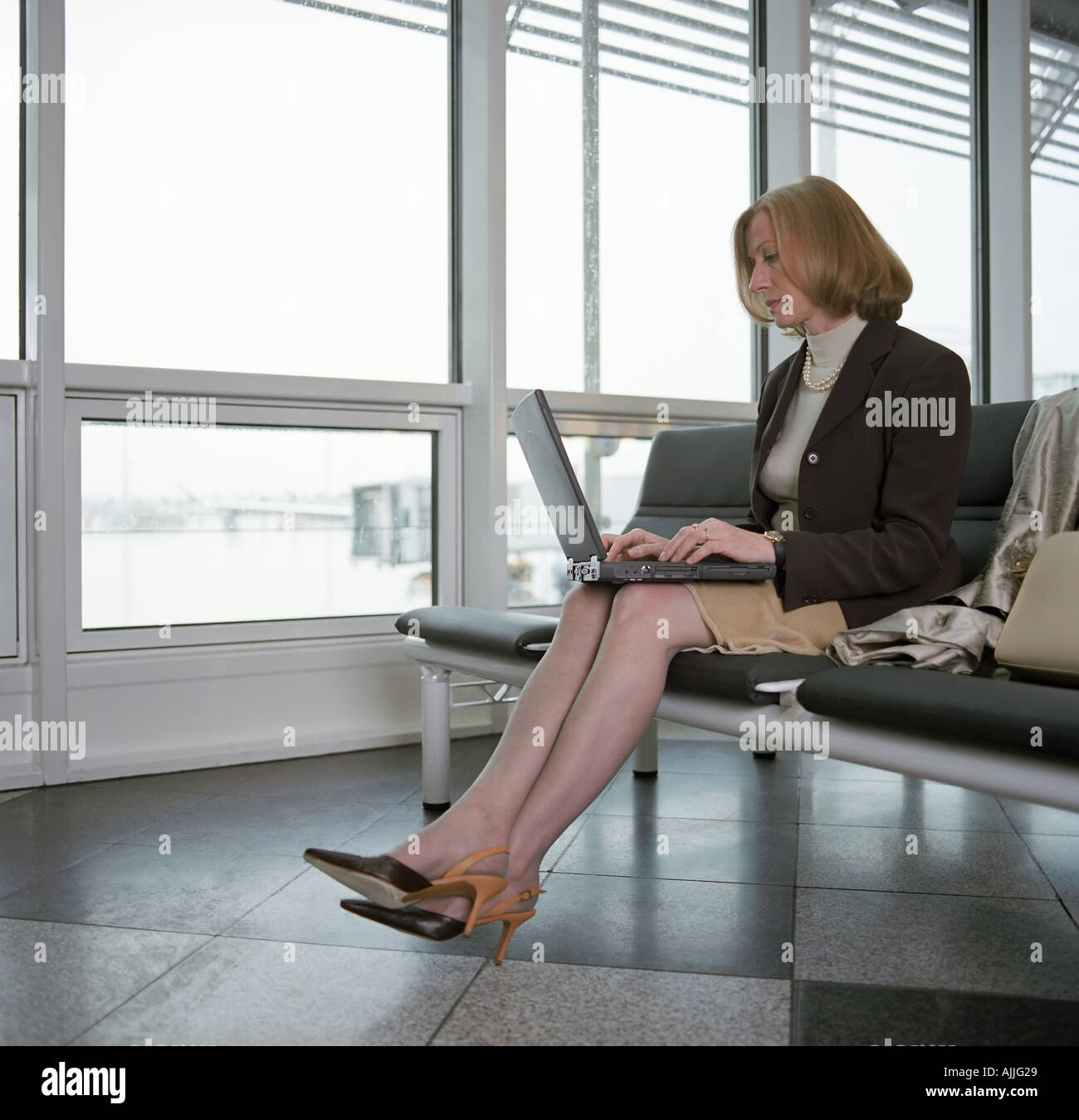 Businesswoman using laptop in departure lounge - Stock Image