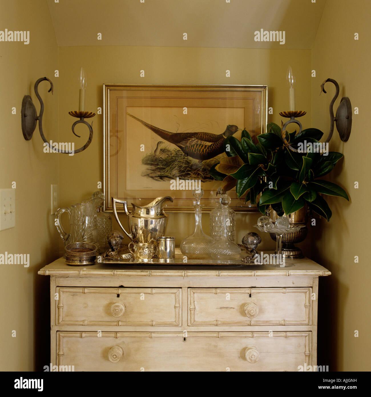 Chest of drawers set in alcove with decanter and silverware in top - Stock Image