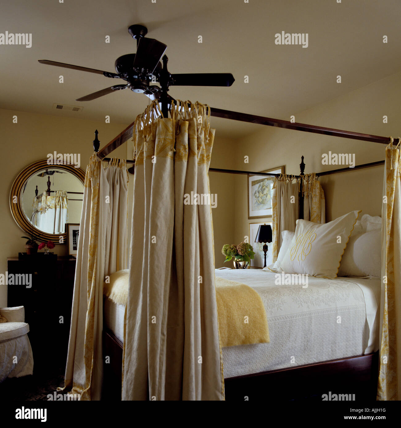 Fourposter Bed With Curtain Rail In Bedroom With Circular Mirror And Ceiling  Fan