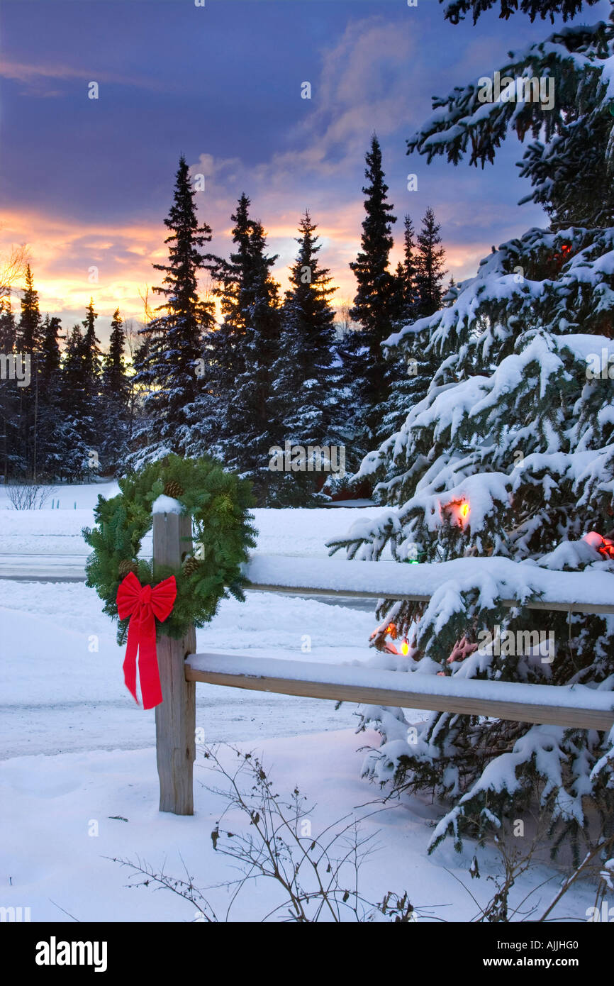 Holiday Wreath hanging on split rail fence next to decorated tree w sunset Anchorage Alaska Winter Stock Photo