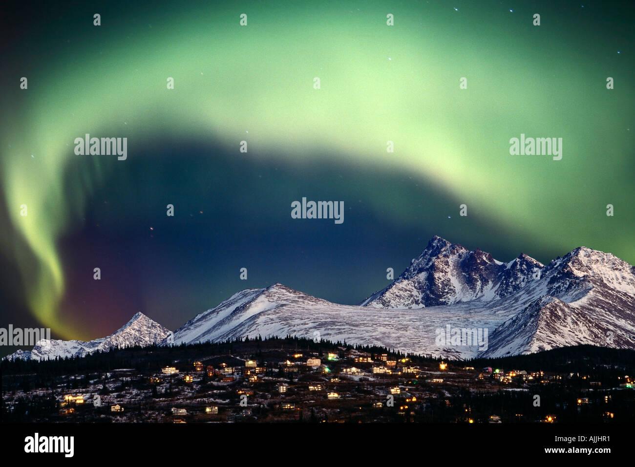 Aurora Borealis over hillside neighborhood Chugach Mountains Anchorage Alaska SC Composite Winter - Stock Image