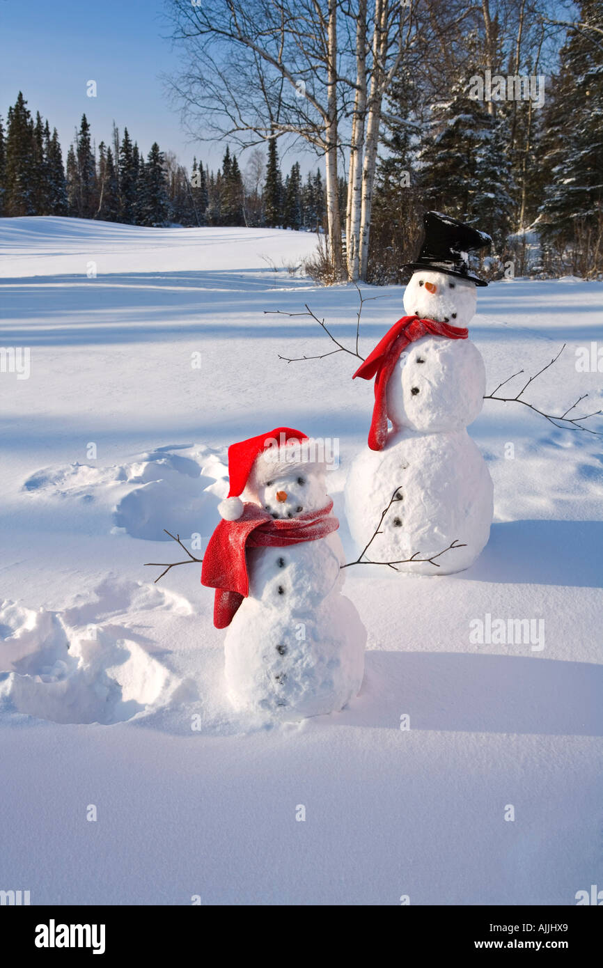 Snowmen in forest after making snow angel imprint in snow Alaska Winter - Stock Image