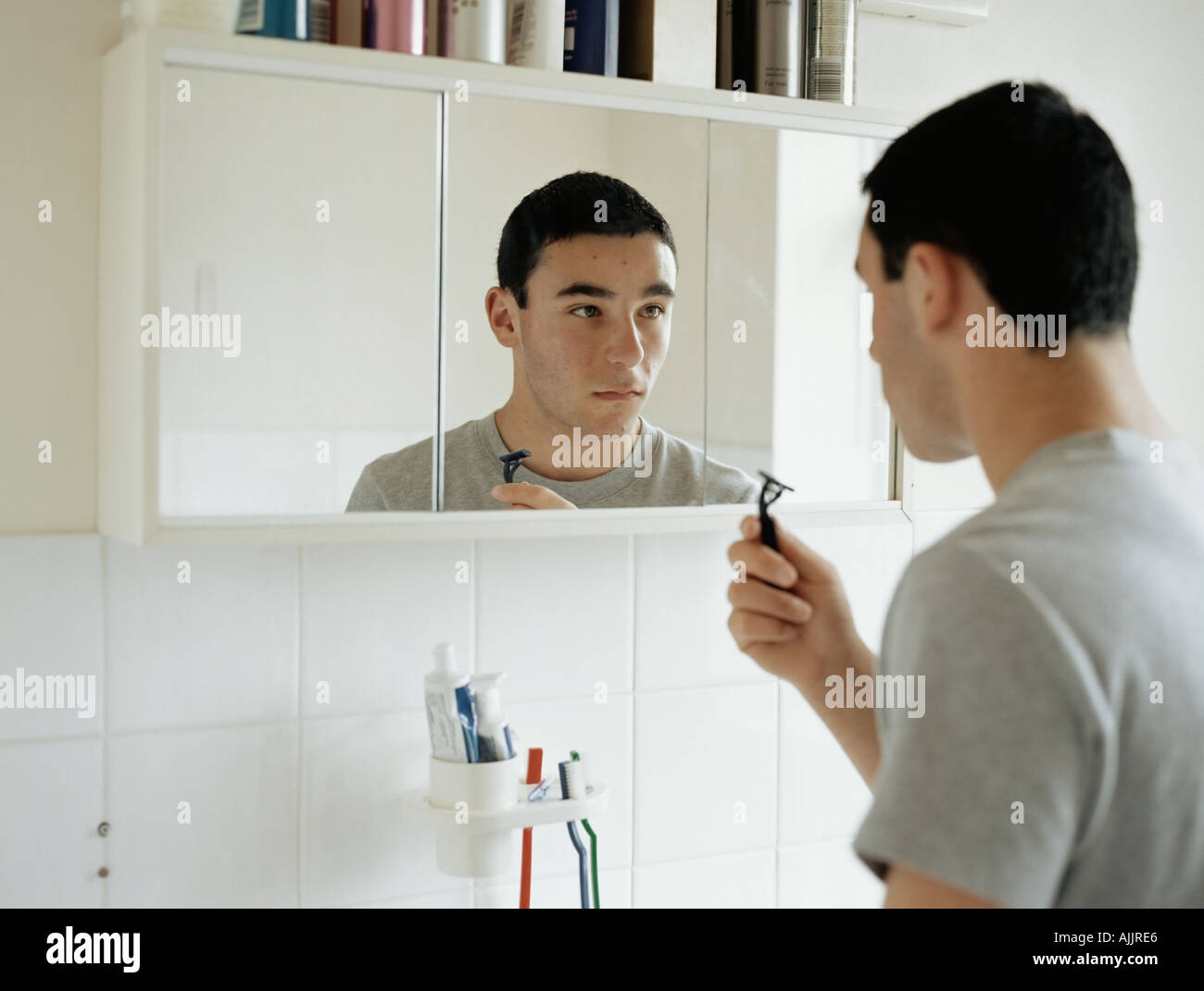 Teenage boy preparing to shave - Stock Image