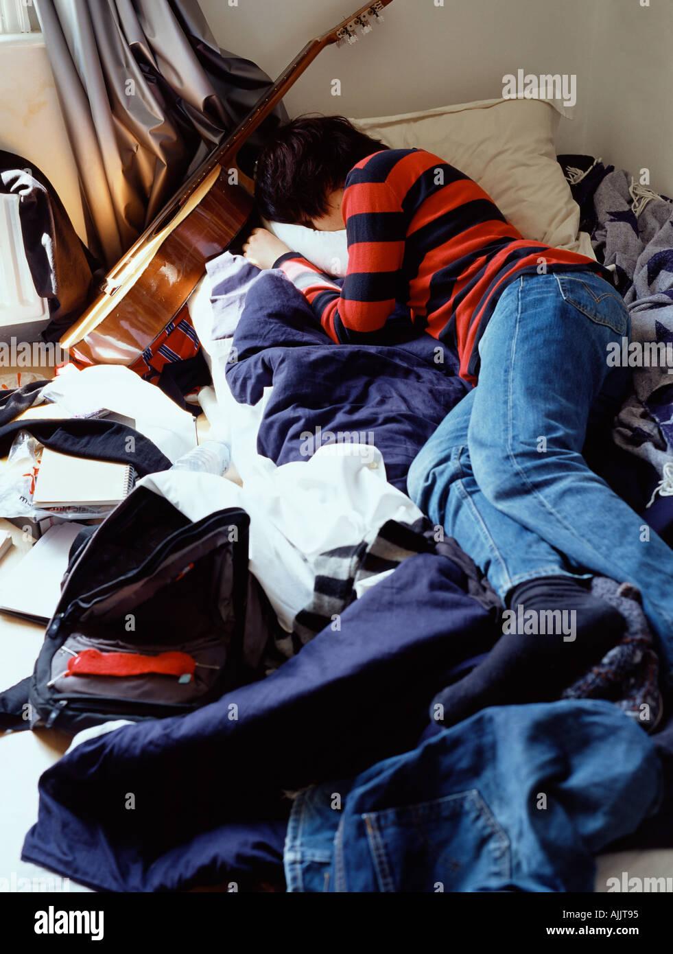 Boy sleeping on messy bed - Stock Image