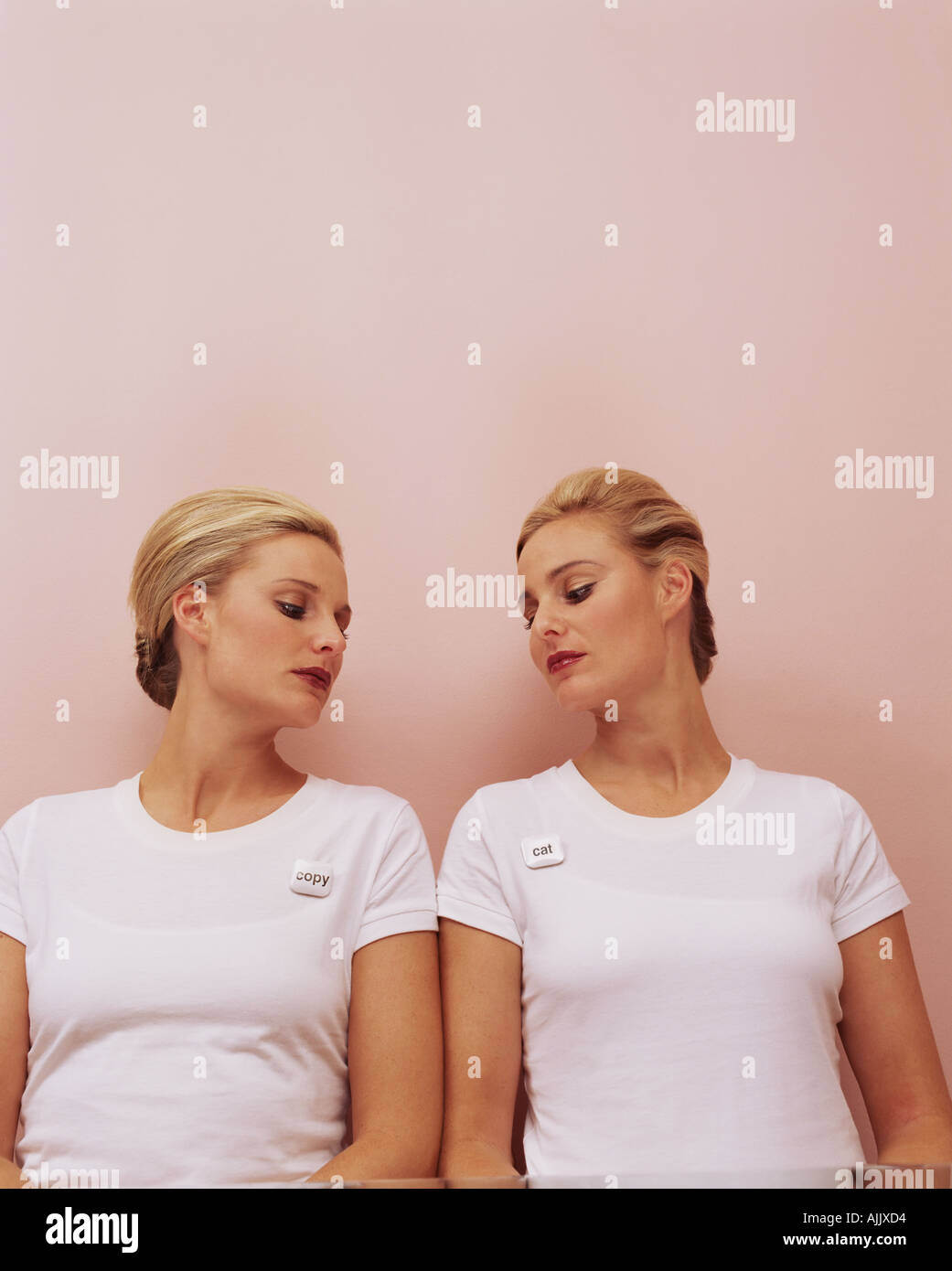 Women looking at each other's badges - Stock Image