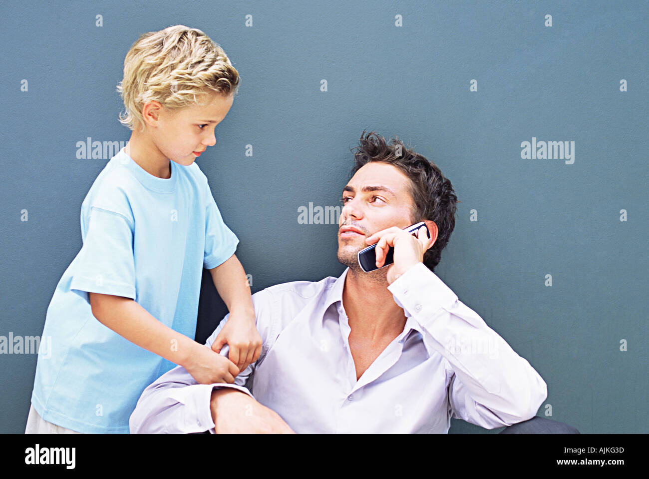 Boy trying to get father's attention - Stock Image