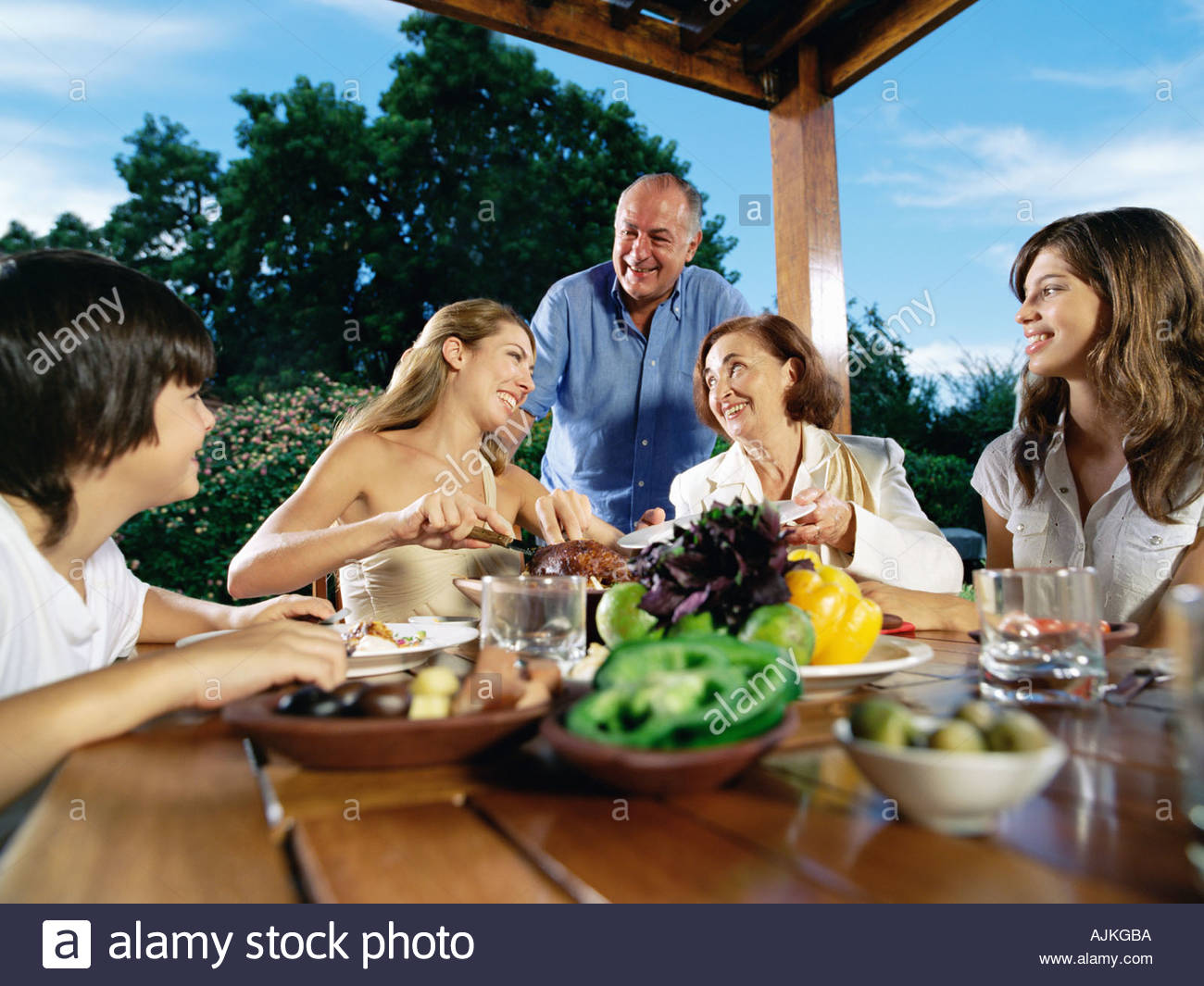 Mother carving meat for family - Stock Image