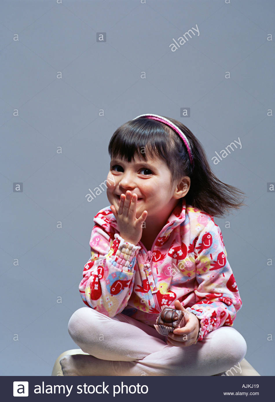 Mischievous girl holding a cup cake - Stock Image