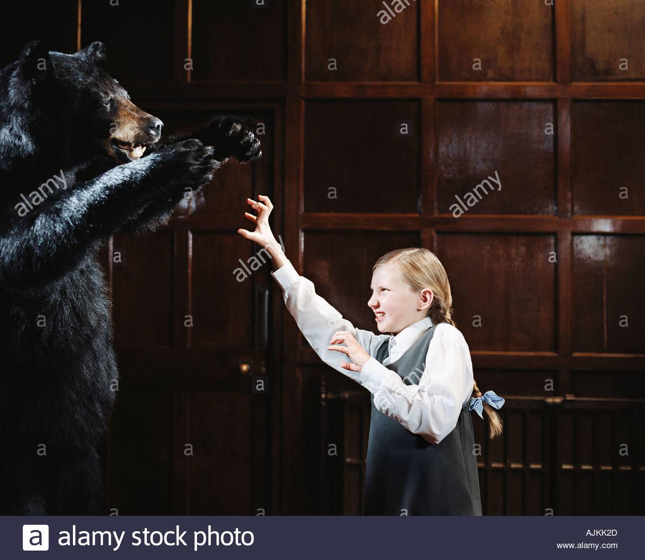 School girl growling at bear - Stock Image