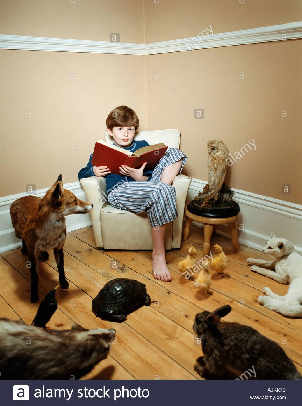 Boy reading story to stuffed animals - Stock Image