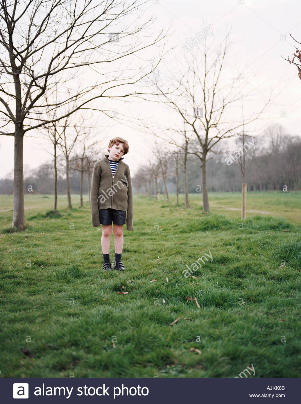 Boy standing in a field - Stock Image