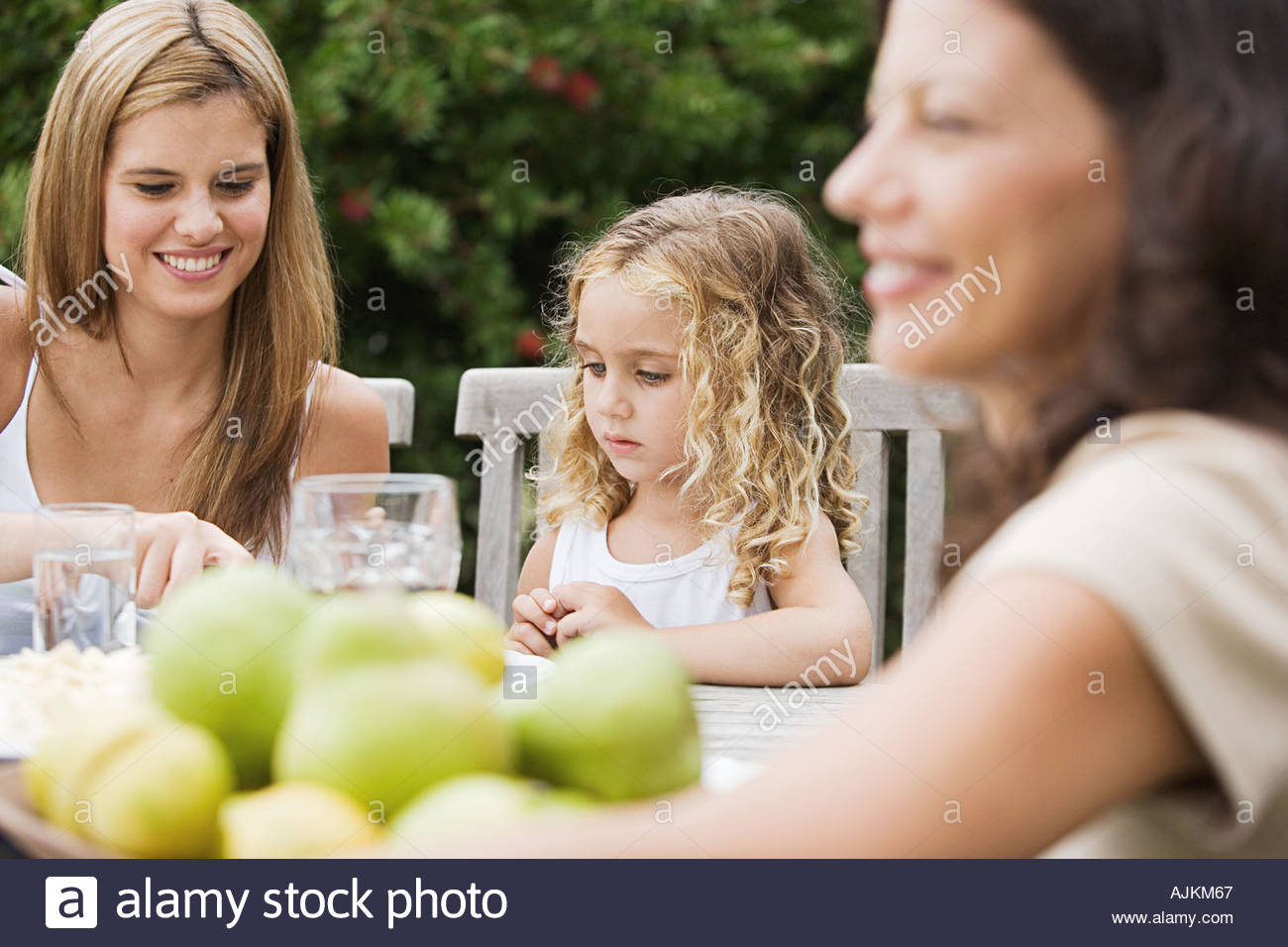Girl at a table in the garden - Stock Image